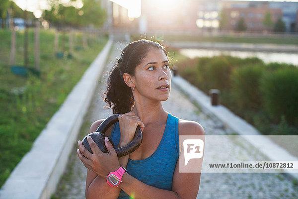 Frau trainiert  Kettlebell am Flussufer halten