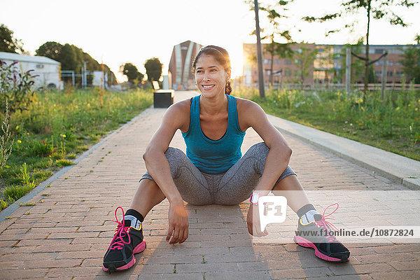 Frau trainiert  sitzt auf dem Bürgersteig und macht eine Pause