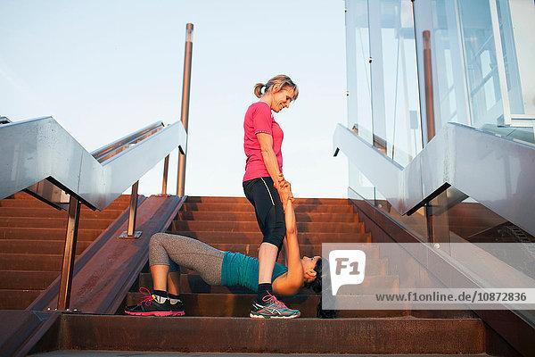 Two women training on stairway