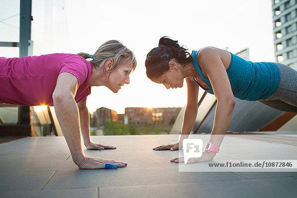 Two women training  doing push ups on stairway