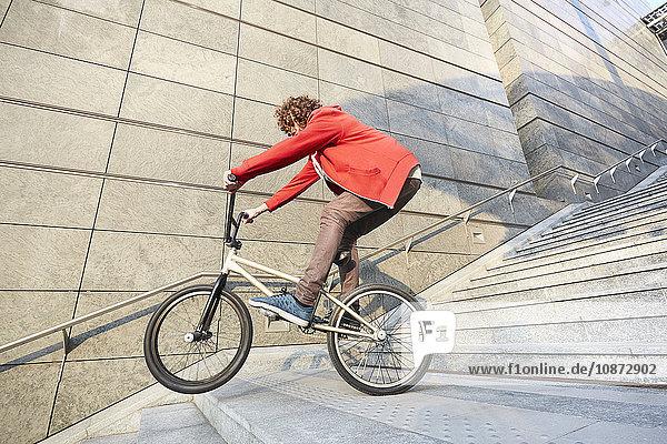 Mann fährt BMX-Stufen im Stadtgebiet