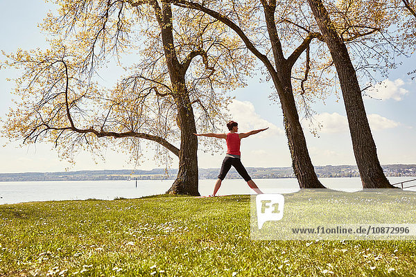 Rückansicht einer Frau  die am See Yoga praktiziert