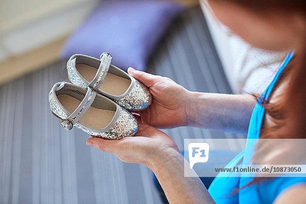 Über-Schulter-Ansicht einer schwangeren Frau mit silbernen Schuhen