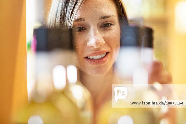 Young woman in wine shop choosing bottle of wine
