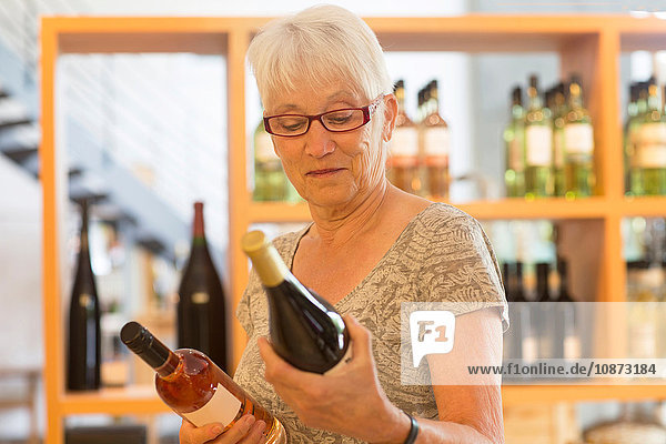 Woman in wine shop selecting bottle of wine