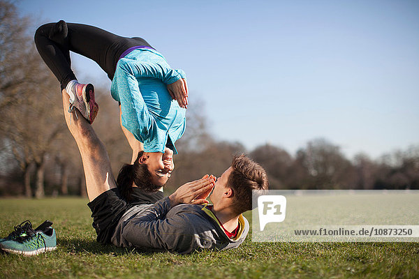 Young woman balancing on top of man practicing yoga pose in park