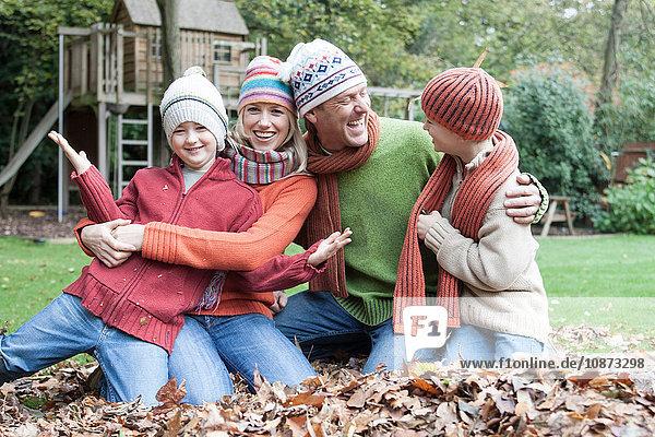Porträt einer Familie  die im Herbstlaub sitzt