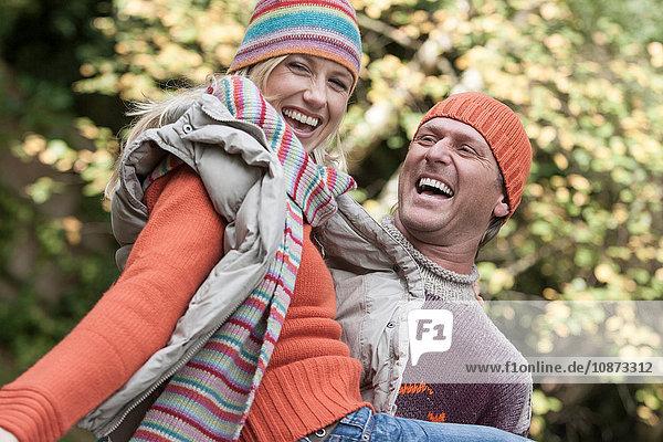 Reifer Mann  tragende Frau  lachend  im Freien