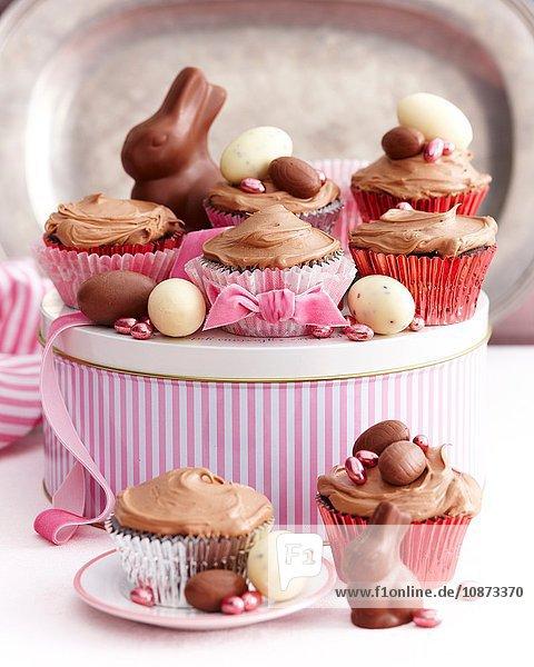 Schokoladenmuffins mit Glasur überzogen und mit Ostereiern dekoriert Schokoladenmuffins mit Glasur überzogen und mit Ostereiern dekoriert