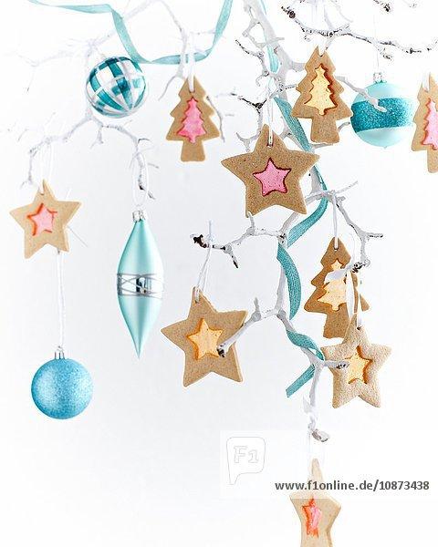 Sternförmige Glasplätzchen und -kugeln  die an einem bemalten weißen Zweig hängen