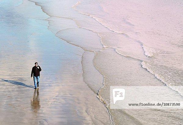 Hochwinkel-Frontansicht eines reifen Mannes  der am Strand entlang der Küste spazieren geht