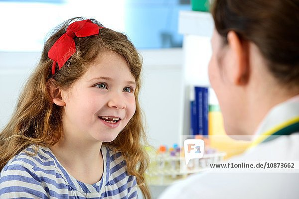 View over shoulder of girl consulting with doctor in clinic  smiling