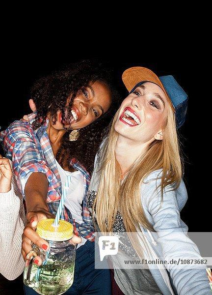 Junge Frauen kauerten sich zusammen und hielten Maurergefäße mit offenem Mund und einem Lächeln
