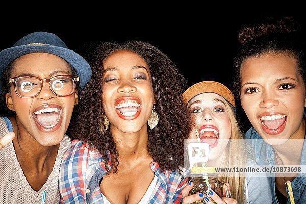 Junge Frauen  die Seite an Seite mit offenem Mund lächelnd in die Kamera schauen
