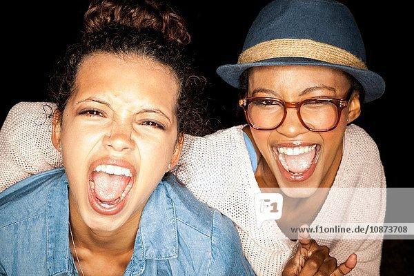 Kopf und Schultern junger Frauen  die mit offenem Mund lächelnd in die Kamera blicken