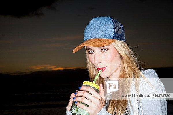 Junge Frau mit Baseballmütze trinkt aus Mason-Glas und schaut lächelnd in die Kamera
