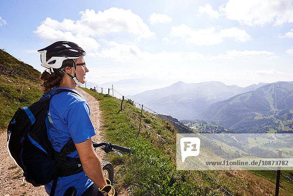 Radfahrer mit Fahrradhelm mit Blick auf die Berge