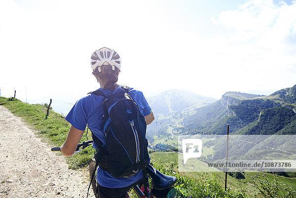 Rückansicht eines Radfahrers mit Fahrradhelm mit Blick auf die Berge