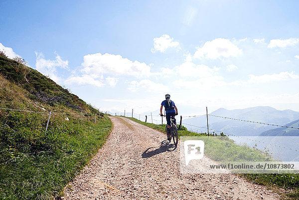 Rückansicht eines Radfahrers auf einem Feldweg in den Bergen