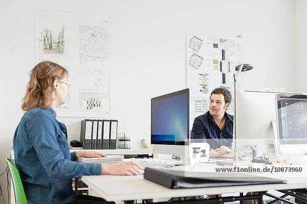 Kollegen  die im Büro am Schreibtisch sitzen und am Computer reden