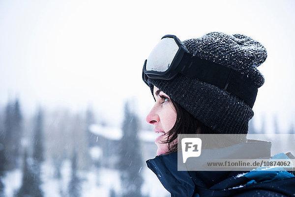 Porträt einer jungen Frau mit Skibrille  die in den Schnee starrt  Brighton Ski Resort ausserhalb von Salt Lake City  Utah  USA