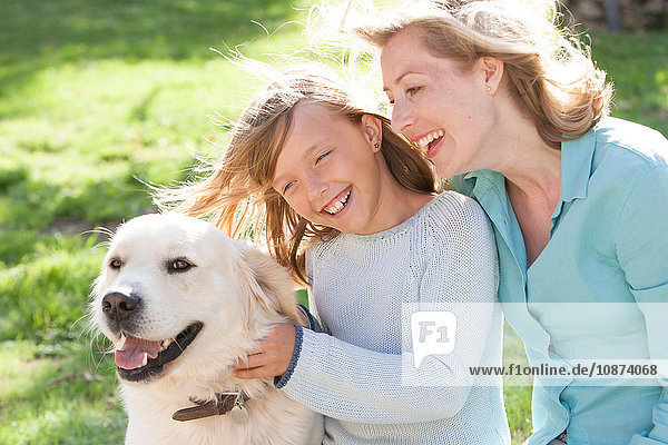 Mother and daughter in garden with dog smiling