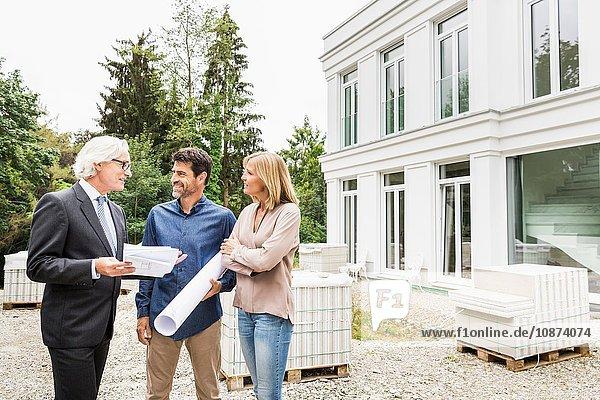 Architekt diskutiert mit Hausbesitzern Entwürfe für Bauarbeiten