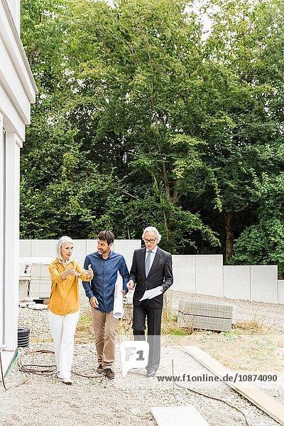 Vorderansicht in voller Länge des Paares  das mit dem Architekten über die Sanierung von Wohnraum diskutiert