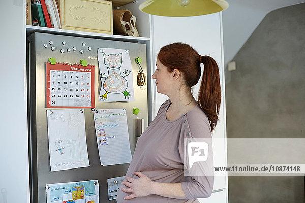 Schwangere Frau schaut auf Kalender am Kühlschrank