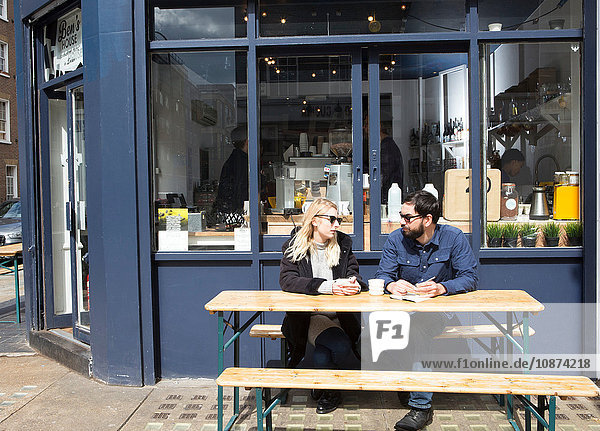 Couple sitting at sidewalk cafe table