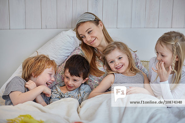 Mother and children together in bed