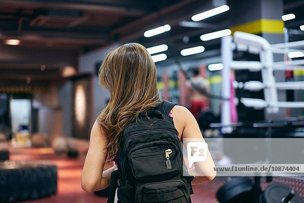 Rear view of young woman carrying backpack preparing for gym