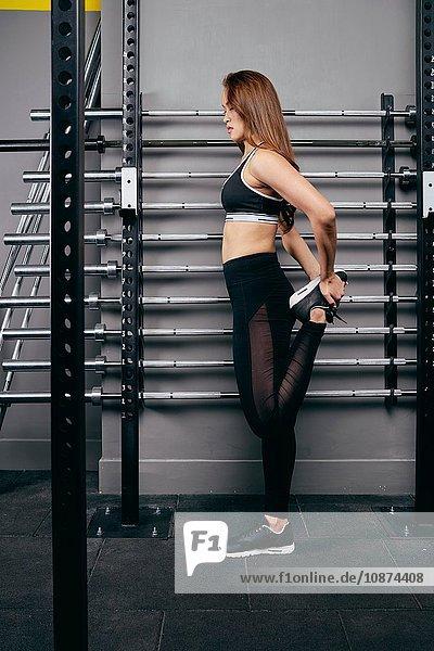Junge Frau beugt Bein beim Aufwärmen im Fitnessstudio
