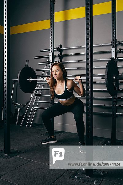 Junge Frau beim Gewichtheben mit Langhantel auf den Schultern im Fitnessstudio