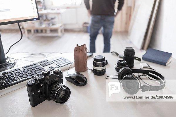 Kamera  Zubehör und Computer auf dem Schreibtisch  Fotograf im Hintergrund