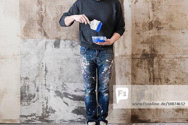 Mann hält Pinsel über Plastikbehälter in der Hand