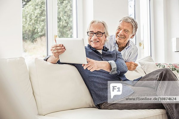 Two men at home  looking at digital tablet