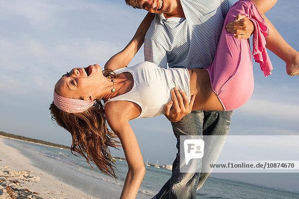 Mann flirtet mit seiner Freundin am Strand herum  Mallorca  Spanien