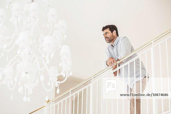 Porträt eines reifen Mannes  zu Hause  an ein Geländer gelehnt