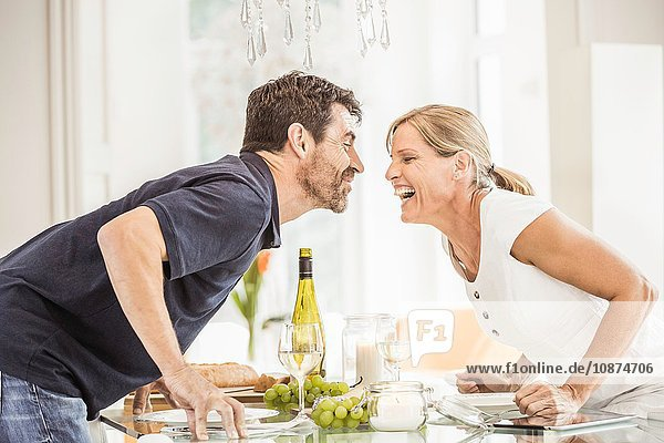 Reifes Paar lehnt über Glastisch  Gesicht an Gesicht  lachend