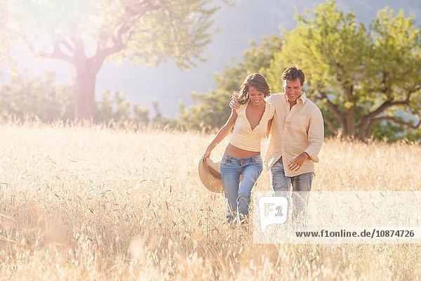 Romantisches Paar beim Spaziergang auf einem Feld aus Langgras  Mallorca  Spanien