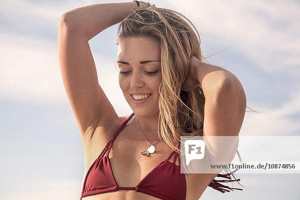 Young woman wearing bikini top with hands in long blond hair  Santa Monica  California  USA