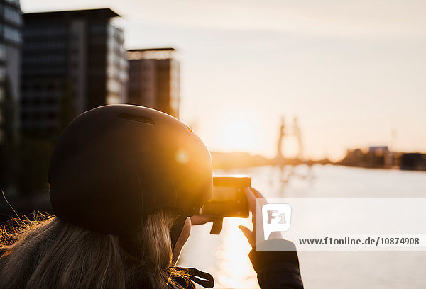 Woman taking photograph of Molecule Man sculpture at sunset  Spree River  Berlin  Germany