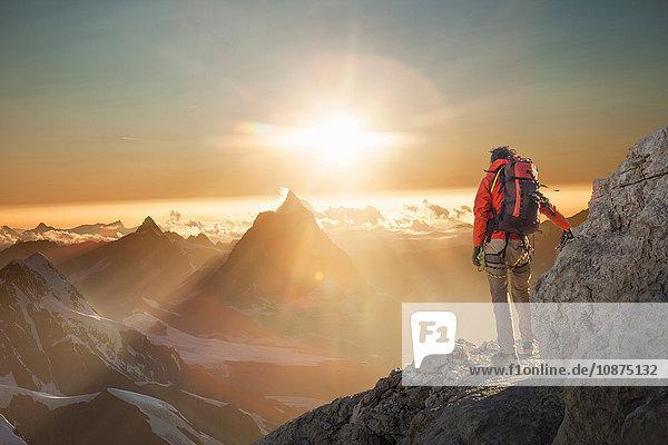 Bergsteiger beobachtet das Matterhorn bei Sonnenuntergang  Zermatt  Kanton Wallis  Schweiz