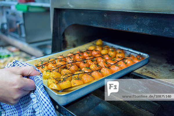 Chef cooking tomatoes in traditional Italian restaurant kitchen  close up