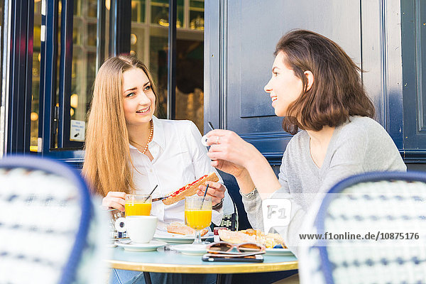 Two young women eating breakfast at sidewalk cafe  Paris  France