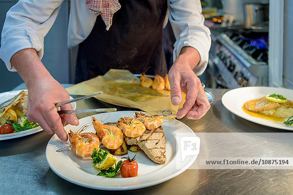 Chef arranging prawn and fish dish in traditional Italian restaurant kitchen