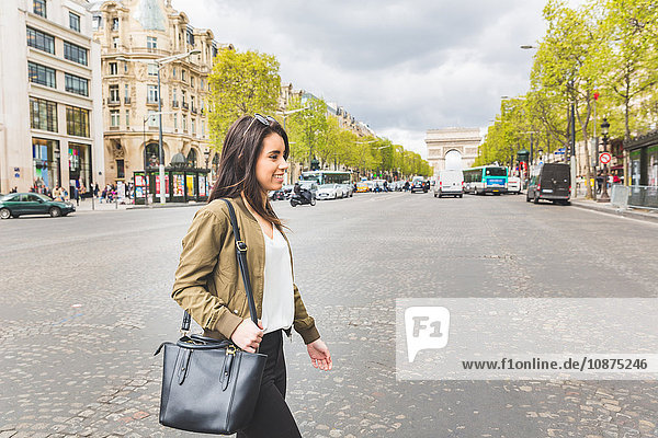 Young woman crossing Champs Elysees  Paris  France