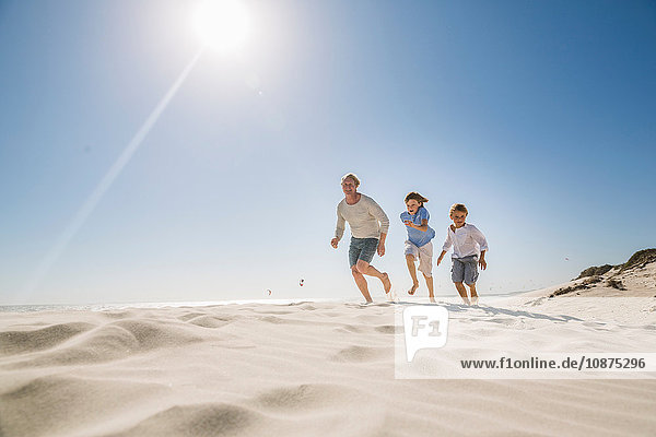 Father and sons running on beach
