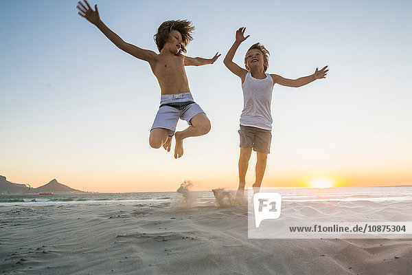 Brothers on beach jumping in mid air at sunset